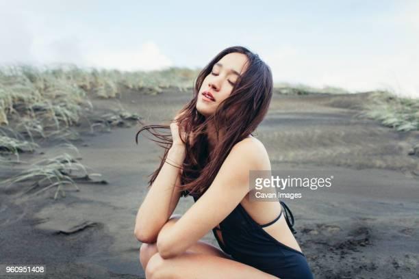 Close-up of beautiful woman crouching on wet beach