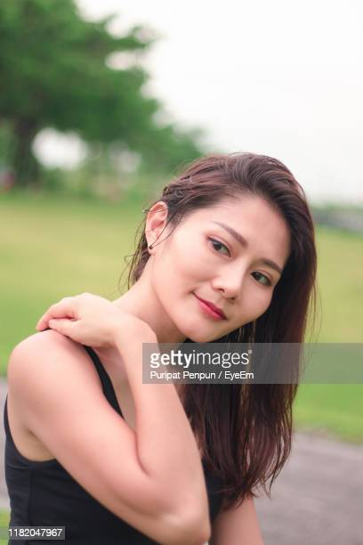 close-up of beautiful woman looking away against trees - thai mueang photos et images de collection