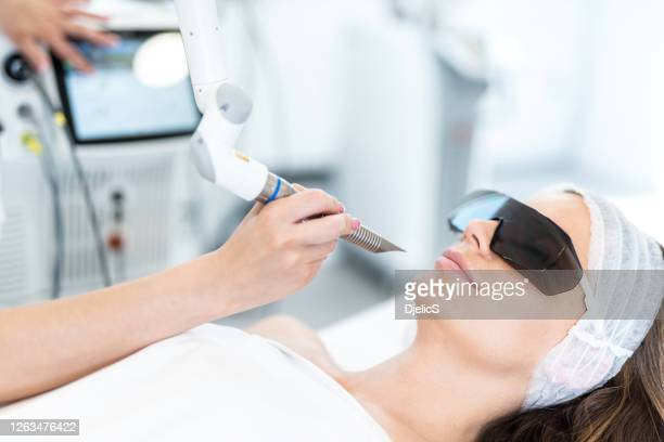 close-up of beautiful woman receiving laser procedures for her face. wearing protection glasses - beauty treatment stock pictures, royalty-free photos & images