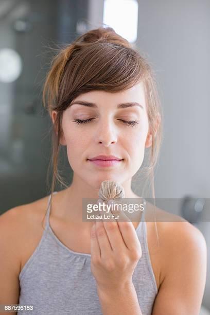 Close-up of beautiful woman smelling tea bag