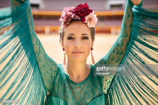close-up of beautiful woman wearing blue dress and flowers with arms raised dancing in bullring - blue dress stock pictures, royalty-free photos & images