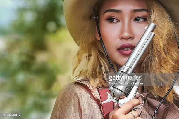 close-up of beautiful woman wearing hat holding gun - cowgirl photos et images de collection