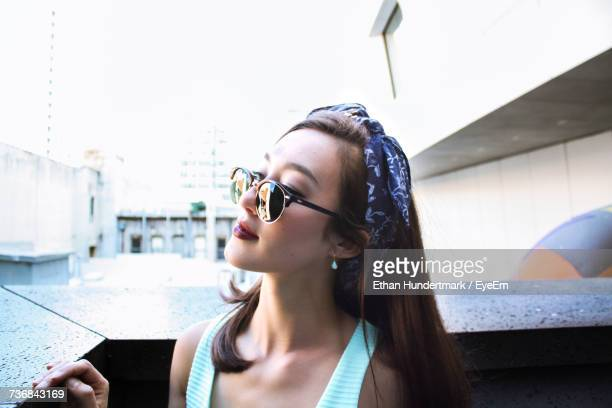 Close-Up Of Beautiful Woman Wearing Sunglasses Looking Away Outside Building