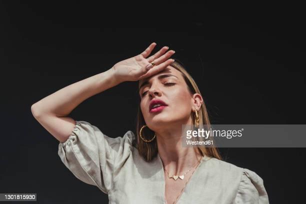 close-up of beautiful woman with eyes closed and hand on head against black background - batom rosa - fotografias e filmes do acervo