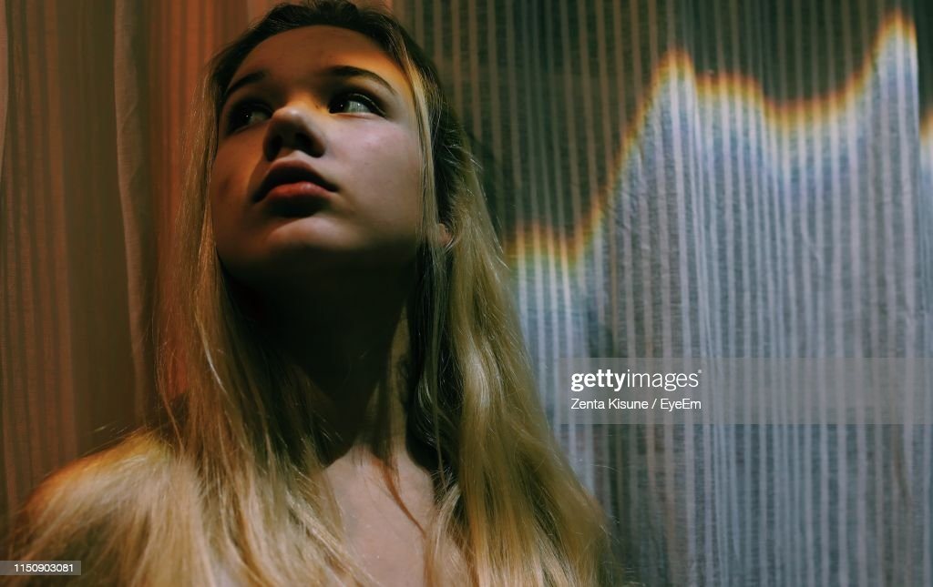 Close-Up Of Beautiful Young Woman Against Curtain At Home : Stock Photo