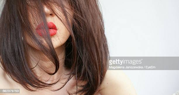 Close-Up Of Beautiful Young Woman Face Covered With Hair Against White Background