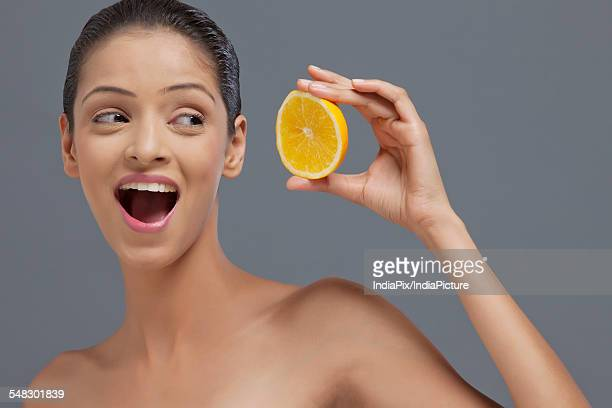 Close-up of beautiful young woman looking at slice of orange