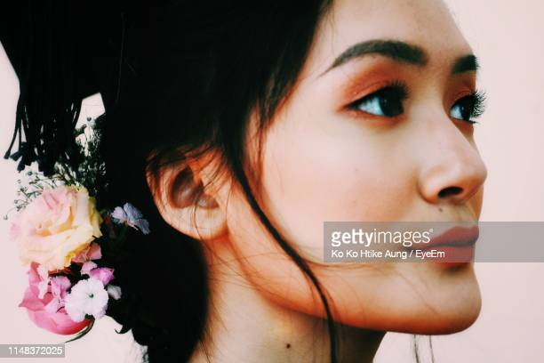 close-up of beautiful young woman looking away against pink background - ko ko htike aung stock pictures, royalty-free photos & images