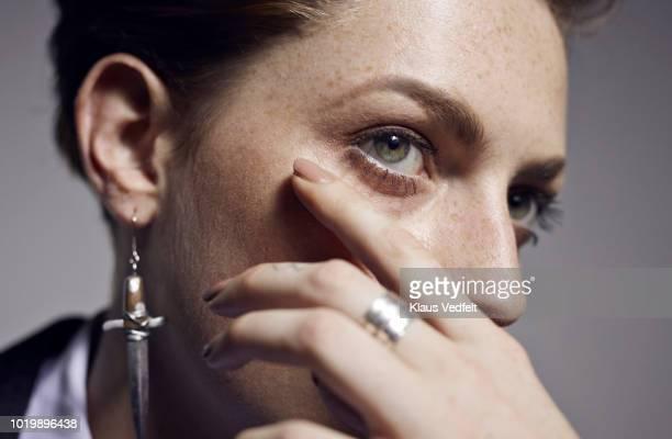 close-up of beautiful young woman's hand and eye, shot on studio - orecchini foto e immagini stock