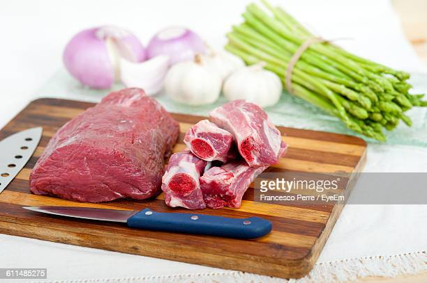 Close-Up Of Beef On Cutting Board With Vegetables On Table