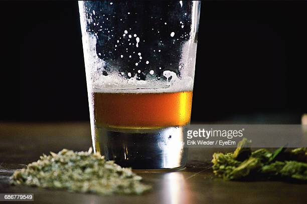 Close-Up Of Beer And Cannabis On Table