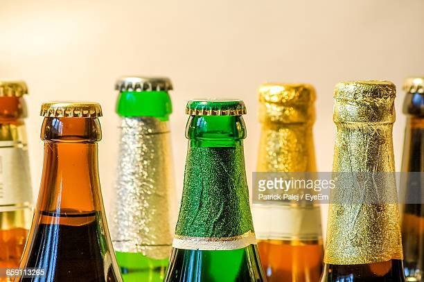 Close-Up Of Beer Bottles Against Wall
