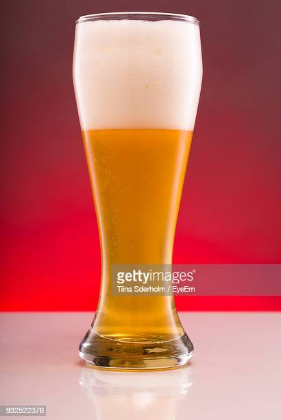 Close-Up Of Beer Glass Against Red Background