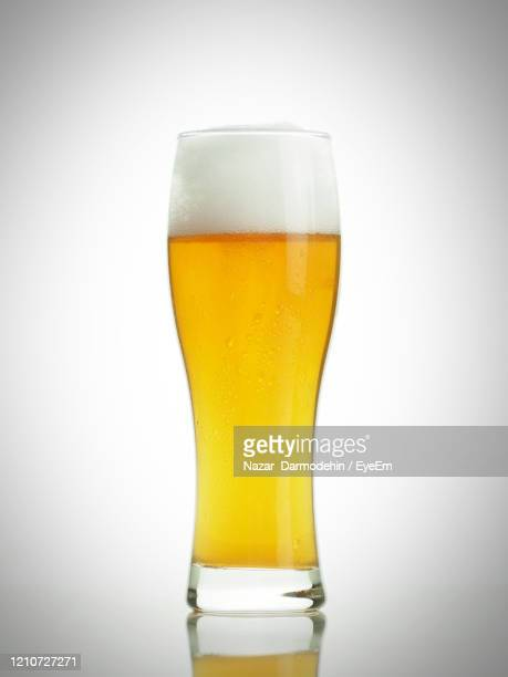 close-up of beer glass against white background - ビアグラス ストックフォトと画像