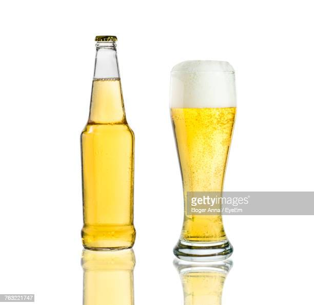 Close-Up Of Beer Glass And Bottle Against White Background