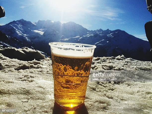 Close-Up Of Beer Glass On Snow Covered Mountain Against Sky