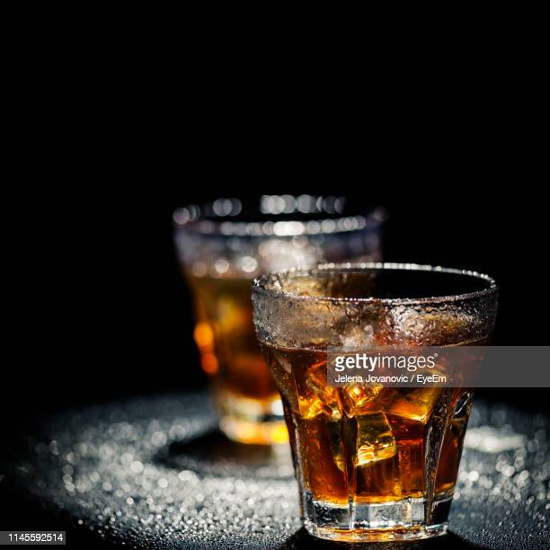close-up of beer glass on table against black background - rum stock pictures, royalty-free photos & images