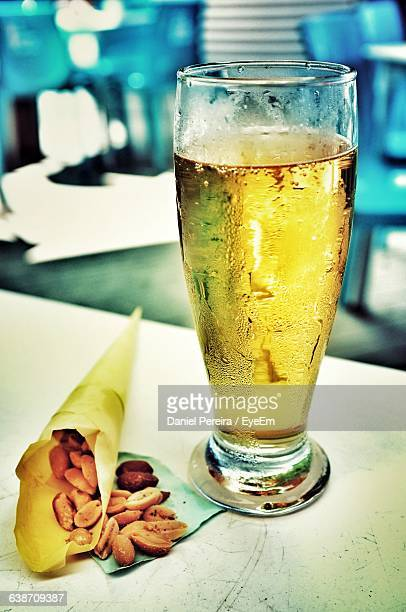Close-Up Of Beer Glass With Peanuts On Table