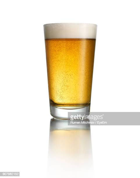 close-up of beer in glass against white background - beer stock pictures, royalty-free photos & images