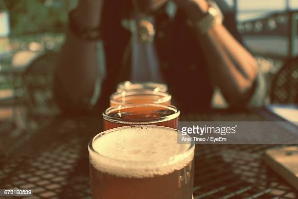 Close-Up Of Beer Served In Row On Table Against Man In Background