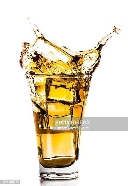 Close-Up Of Beer Splashing In Glass Against White Background