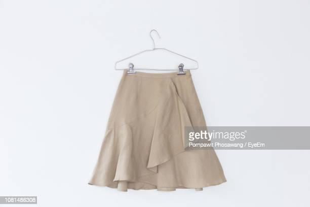 close-up of beige skirt on coathanger against white background - up skirts stock pictures, royalty-free photos & images