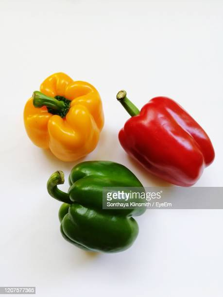 close-up of bell peppers against white background - green bell pepper stock pictures, royalty-free photos & images