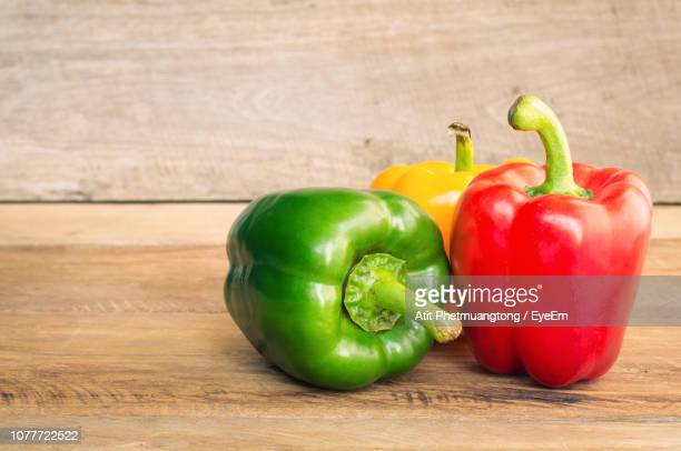 close-up of bell peppers on wooden table - yellow bell pepper stock pictures, royalty-free photos & images