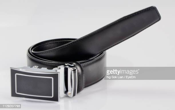 close-up of belt against gray background - silver belt stock pictures, royalty-free photos & images