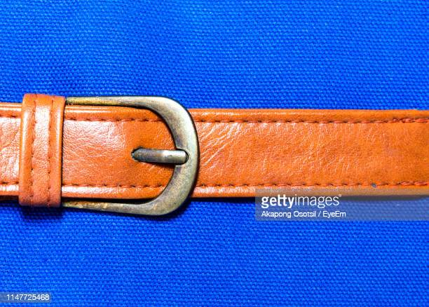 close-up of belt on blue background - leather belt stock pictures, royalty-free photos & images
