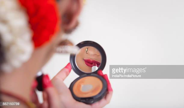 Close-up of Bharatanatyam dancer applying lipstick in compact mirror over white background