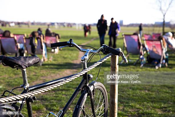 close-up of bicycle by rope fence on field - tempelhof airport stock pictures, royalty-free photos & images