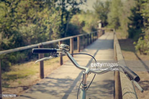 close-up of bicycle on railing against trees - handlebar stock pictures, royalty-free photos & images