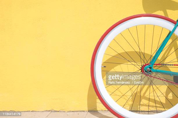 close-up of bicycle parked by yellow wall - wheel stock pictures, royalty-free photos & images