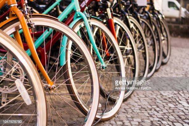 close-up of bicycle parked on paving stone - bicycle stock pictures, royalty-free photos & images