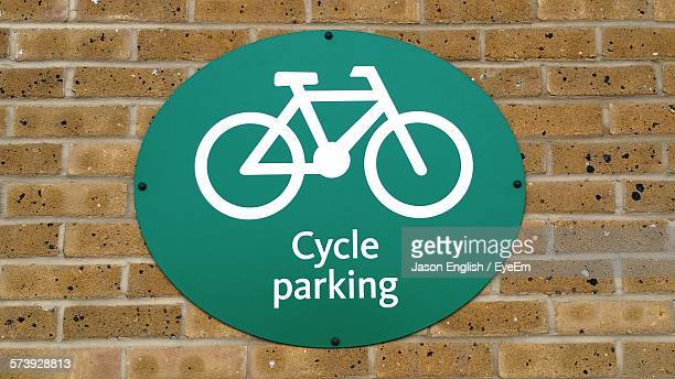 Close-Up Of Bicycle Parking Sign On Brick Wall