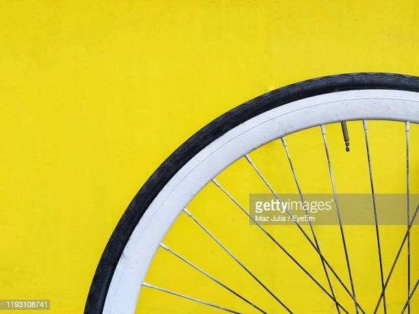 close-up of bicycle wheel against yellow background - wheel stock pictures, royalty-free photos & images