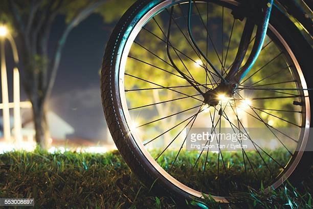 Close-Up Of Bicycle Wheel On Grassy Field At Illuminated Park