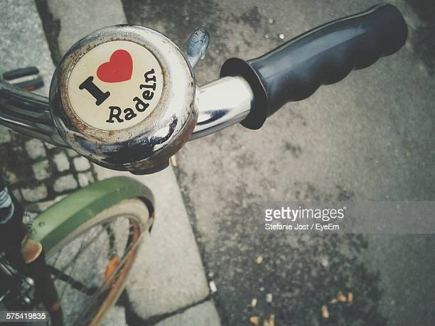 close-up of bicycle with heart shape and text on bell - glocke stock-fotos und bilder