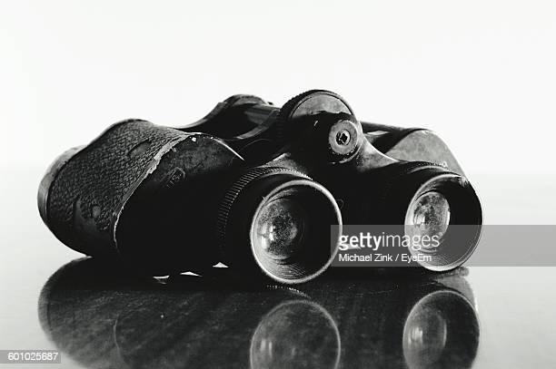 Close-Up Of Binoculars On Table Against White Background