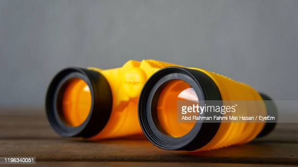close-up of binoculars on table - binoculars stock pictures, royalty-free photos & images