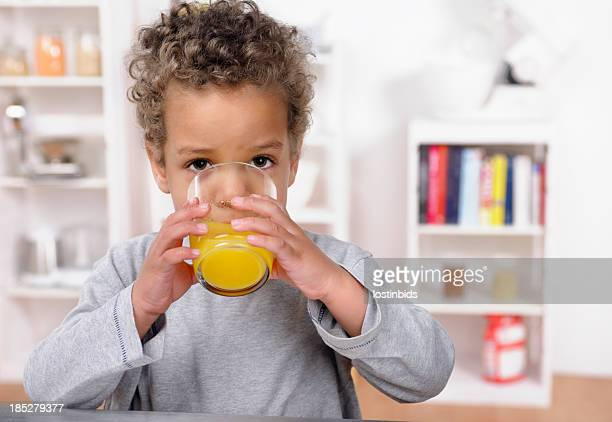 Close-up Of Biracial Toddler Drinking Orange Juice
