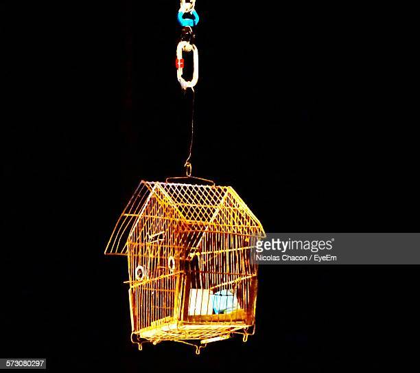Close-Up Of Bird Cage Against Black Background