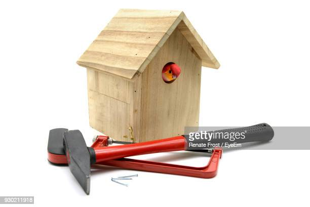 close-up of birdhouse with hand tools on white background - birdhouse stock pictures, royalty-free photos & images