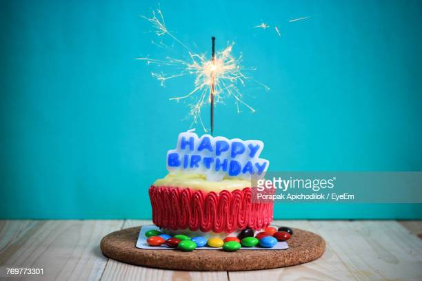 close-up of birthday cake on table against turquoise wall - happy birthday stock pictures, royalty-free photos & images