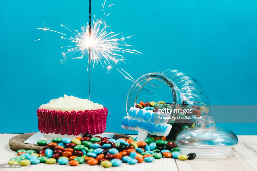 Closeup Of Birthday Cake On Table Against Turquoise Wall Stock Photo