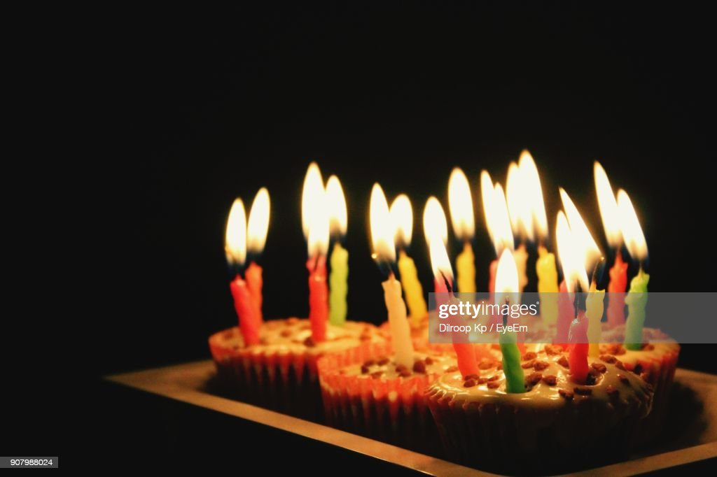 Closeup Of Birthday Cakes On Table Against Black Background Stock