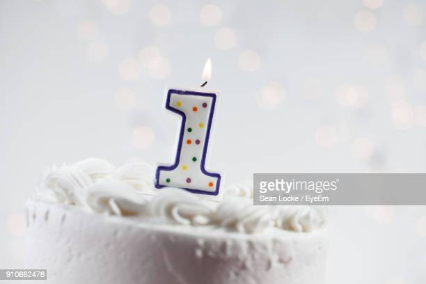 Close-Up Of Birthday Candles On Cake Against White Background