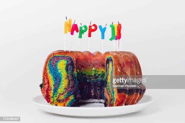 Close-up of birthday candles on rainbow cake in plate against white background