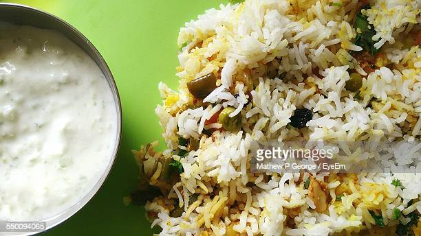 Close-Up Of Biryani With Curd Served On Table